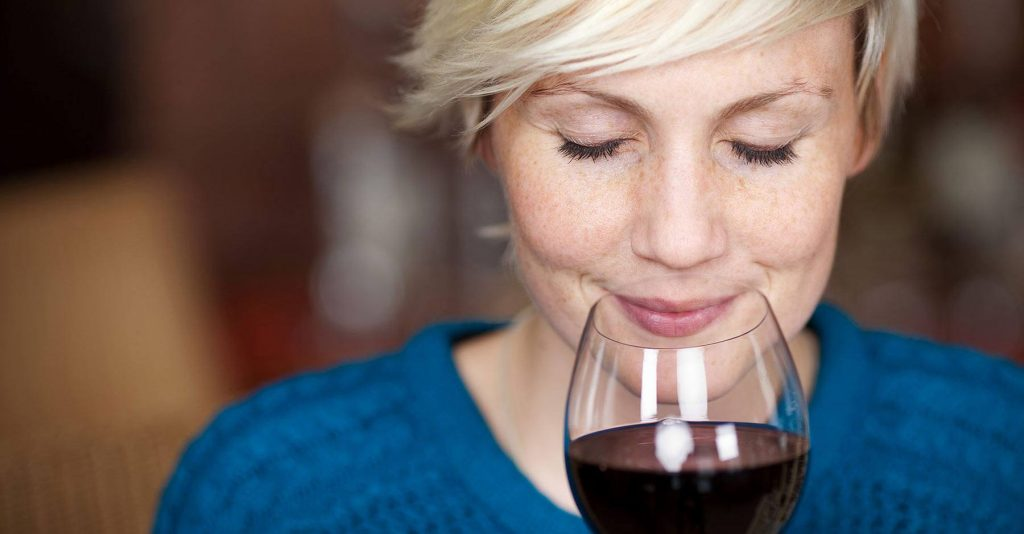 a woman smelling a red wine glass